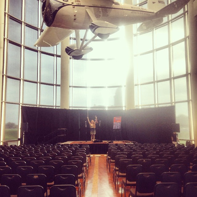 Minna Biggs stands on stage preshow at the Oklahoma History Museum. Wiley Post's famous Winnie Mae airplane hangs overhead.