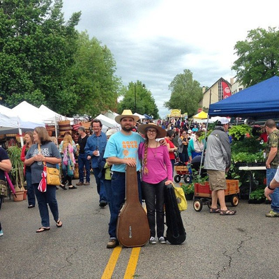 Casey & Minna with fiddle and guitar in cases at the Sand Springs Herbal Affair. Colorful tents and people fill the street.