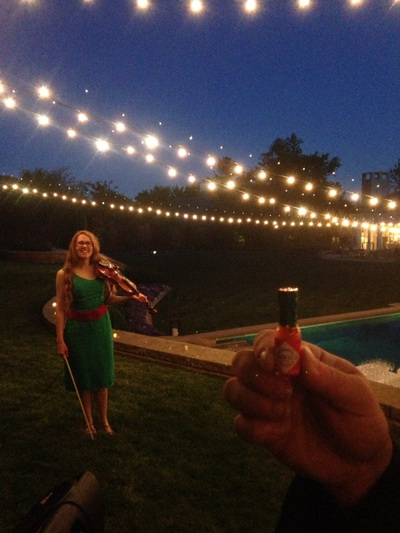 At twilight, elegantly dressed in green, Minna Biggs holds a violin, standing on lush grass, pool side at a private party in Nichols Hills. In the foreground a hand holds a mini Tabasco sauce bottle. String lights twinkle overhead.