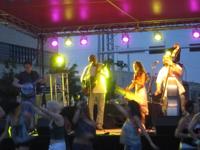 At twilight under stage lights, Casey & Minna play fiddle and upright bass at the Pride Festival OKC as Honkytonk Stepchild.