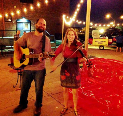 Casey Friedman and Minna Biggs play fiddle and guitar at the Wedge pizza restaurant in the Deep Deuce district in Oklahoma City.