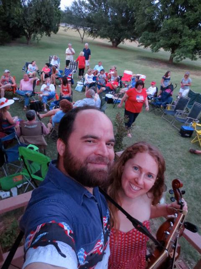 Oklahoma fiddle and guitar duo, Casey & Minna, take a selfie at the 2014 Deer Creek 4th of July private party. A hometown crowd dressed in red, white, and blue mingle among lawn chairs on the grass.