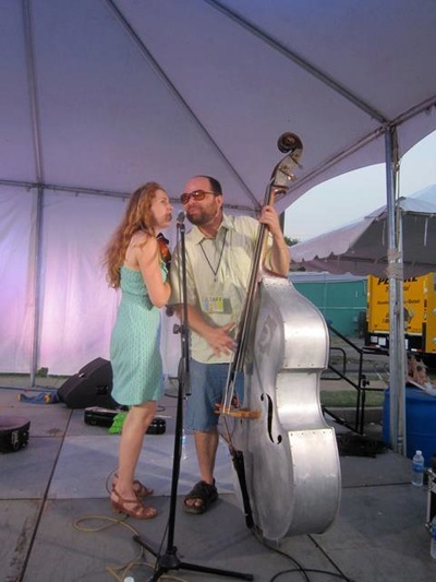 With metal upright bass and fiddle, Casey & Minna sing into the same mic on stage at the Paseo Festival in Oklahoma City.