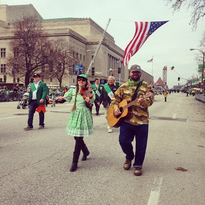 Casey & Minna, Oklahoma folk musicians, march with fiddle and guitar in the Saint Louis Saint Patrick's Day Parade.