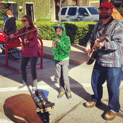 On a chilly April morning on the opening day of the Cherry Street Farmers Market in Tulsa Oklahoma Casey, Minna and August Biggs play music on fiddle, guitar, and tin whistle. Ten year old August looks quit cold; he tries to conserve heat nestled in his bright green hoody.